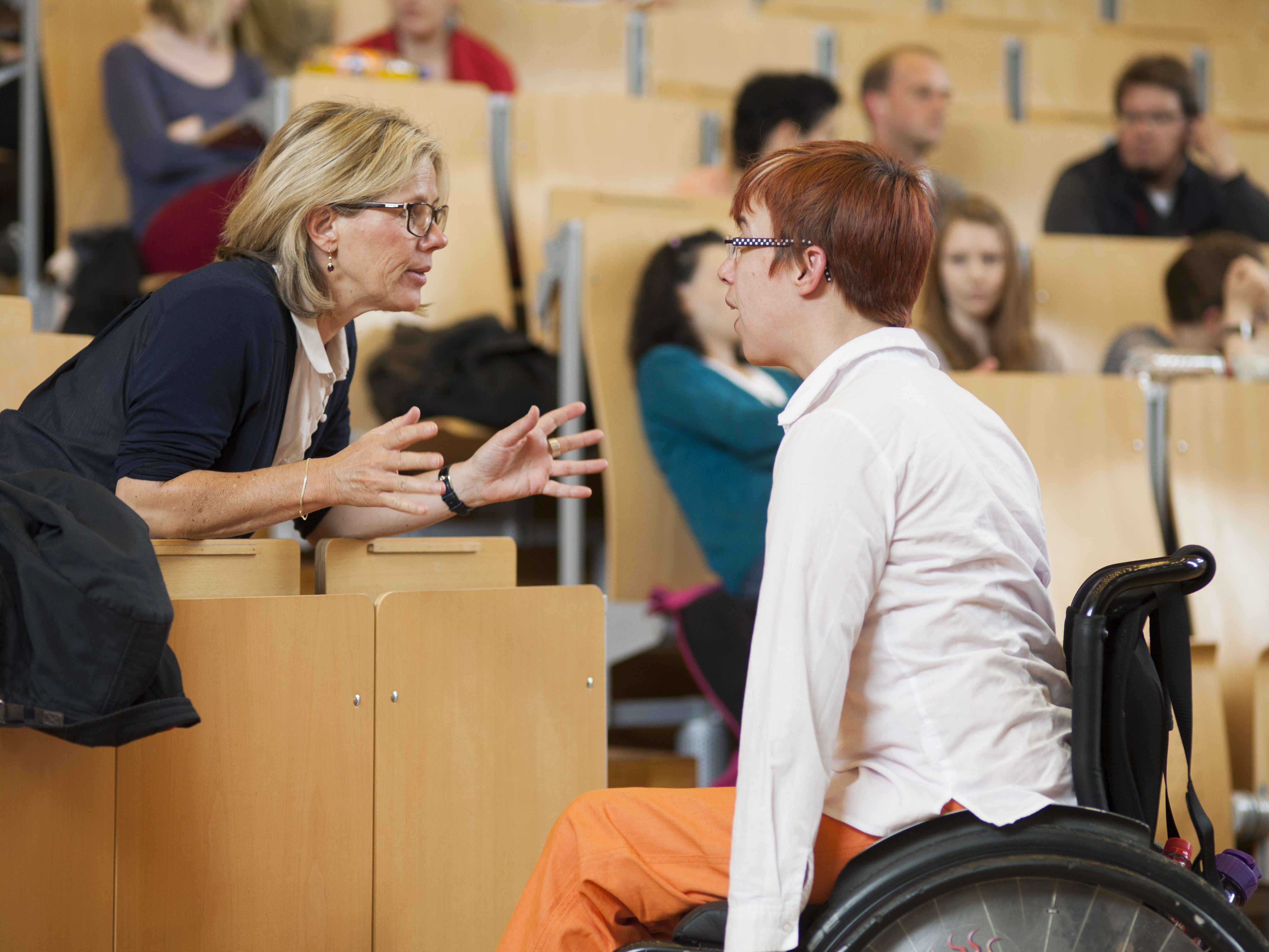 A professor talks to an educational specialist in an auditorium.